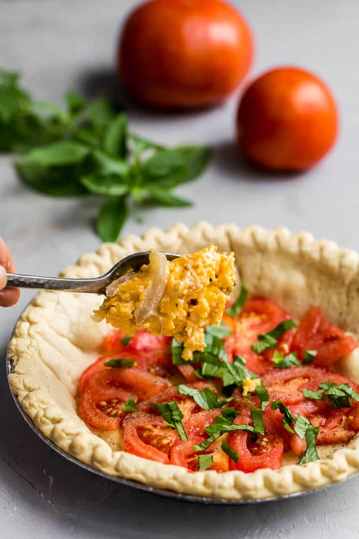 Adding ingredients for tomato pie