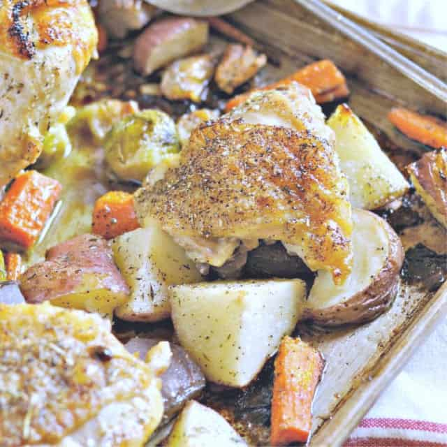 A full bone in chicken thigh in sheet pan with carrots and potatoes