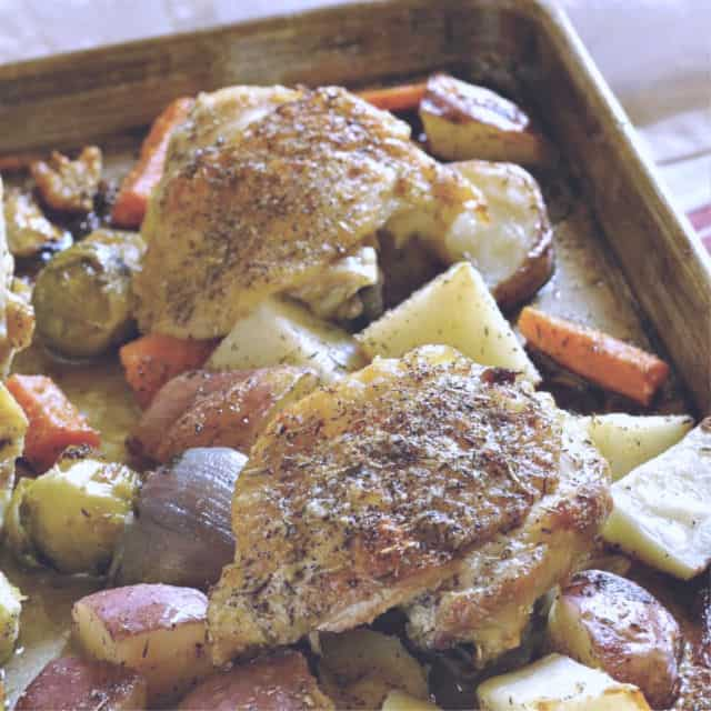 Two Chicken thighs with crispy skin on a sheet pan with veggies