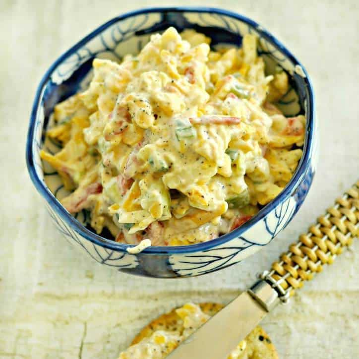 small blue bowl of pimento cheese with spreading knife in background