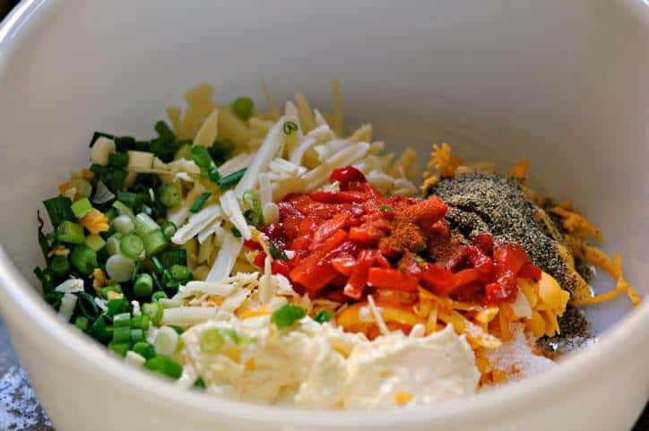 White bowl with all of the ingredients in it showing green onions, white mayo, red pimentos and yellow cheese.