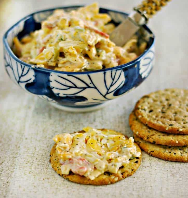 Side view of blue bowl of easy pimento cheese recipe with spreading knife and crackers