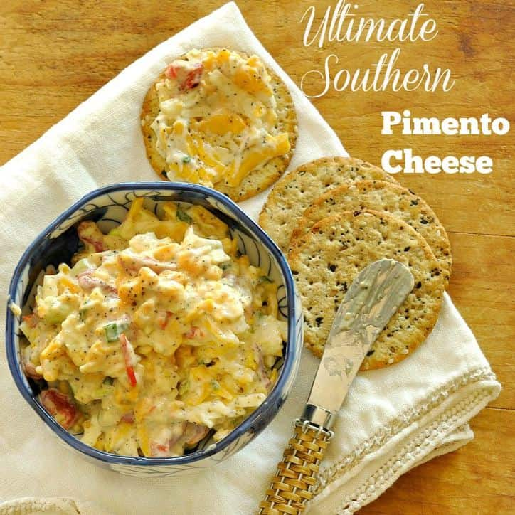 bowl of pimento cheese and 4 crackers one with cheese spread on it, small knife in background