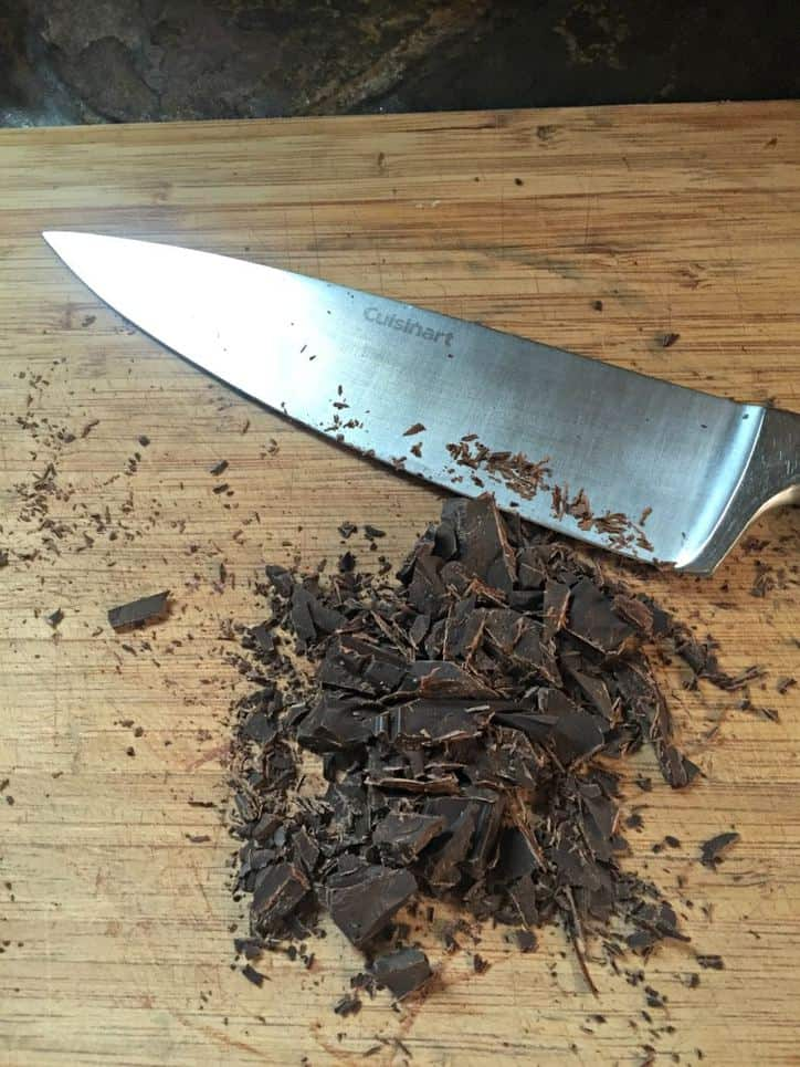 Large knife on cutting board with chopped chocolate pieces