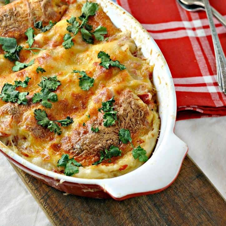 Red baking dish with easy cheesy white chicken enchiladas and a red napkin