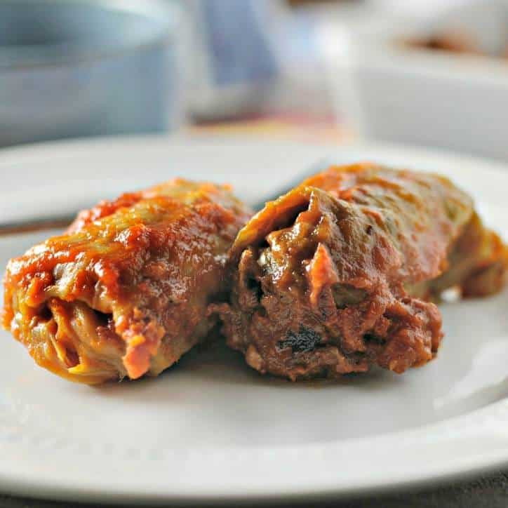 Two whole stuffed cabbage rolls on a white plate