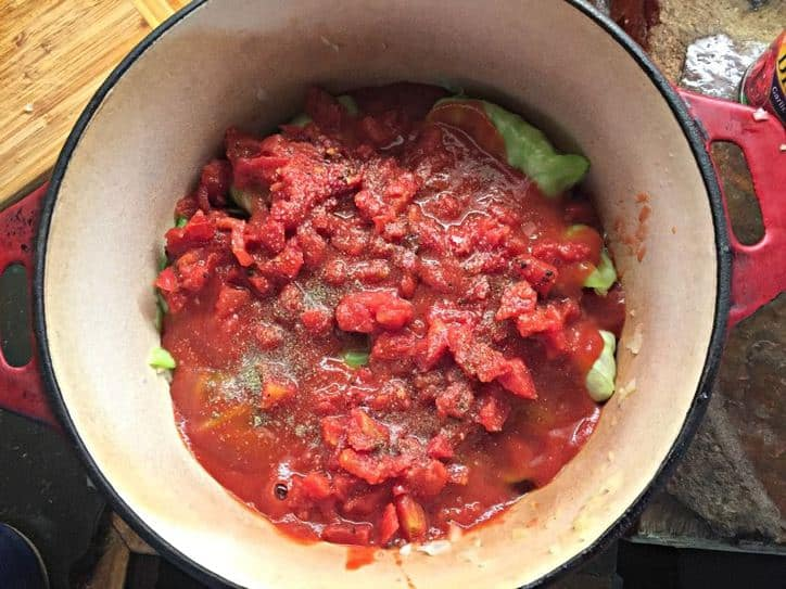 dutch oven with cabbage rolls covered with diced tomatoes