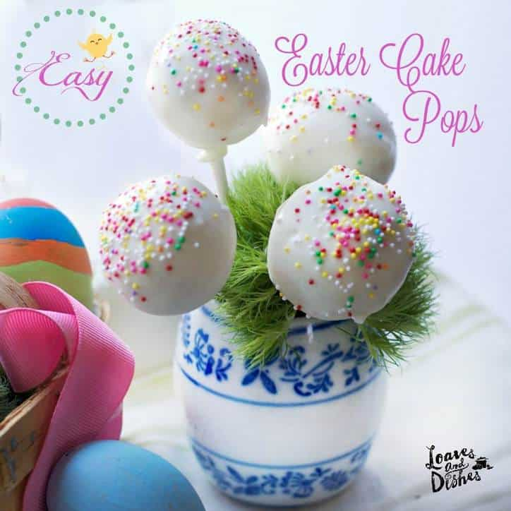 White cake pops with rainbow sprinkles in a blue and white jar. Easter Eggs in foreground