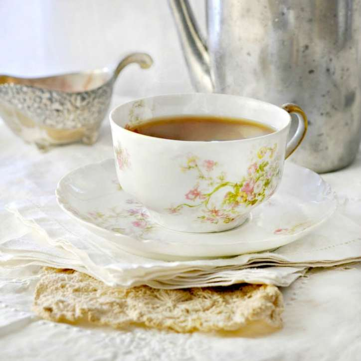 A cup of tea in a bone china cup with saucer, and linen cloth napkins with silver tea pot and sugar bowl in back ground