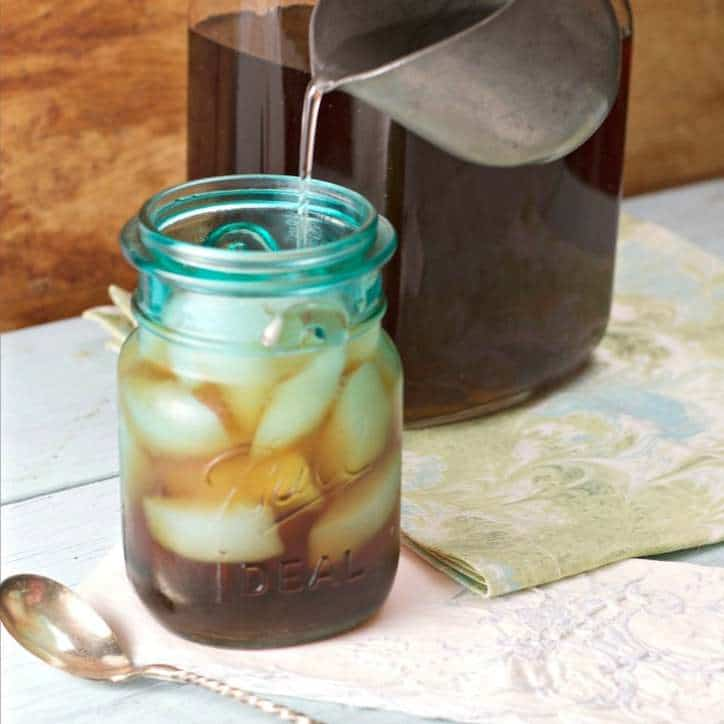 blue mason jar of tea and ice, pitcher in background and spoon in foreground