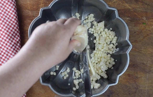 Large knife cutting kernels from the ear of corn into a bundt pan
