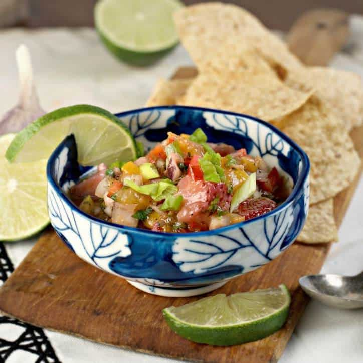 blue bowl of peach salsa with lime and chips