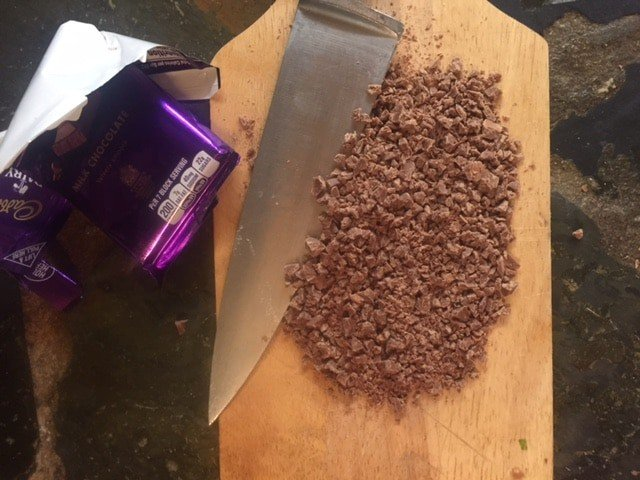 milk chocolate bar chopped super small on a cutting board
