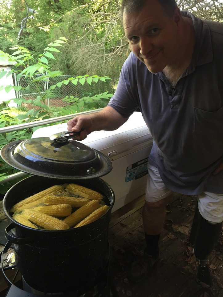 man holding lid off of large pot of corn