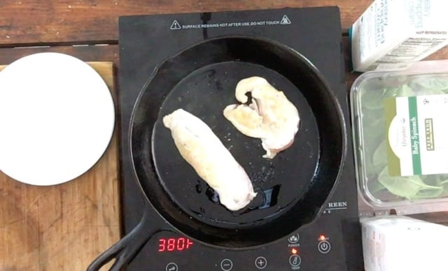 Two chicken breasts frying in a black frying pan