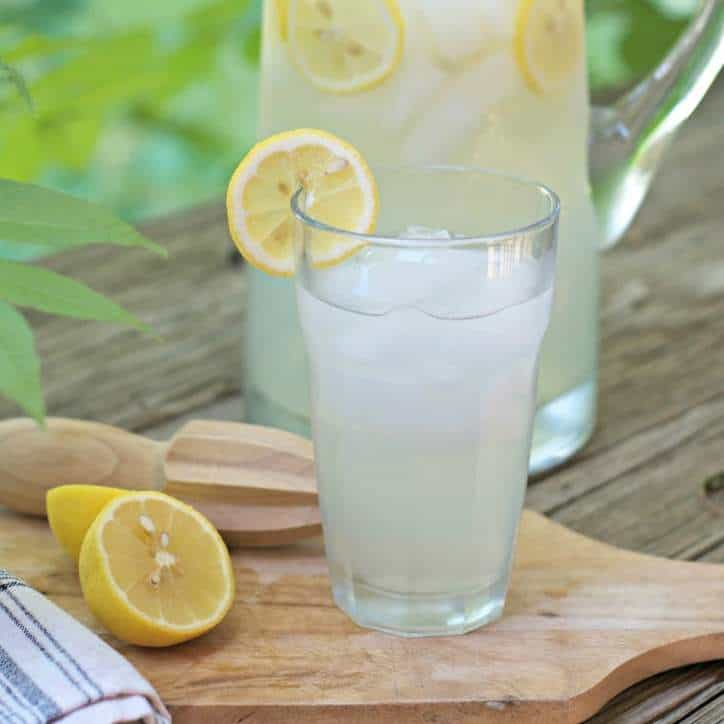 A photo of FRESH HOMEMADE LEMONADE CONCENTRATE in a glass with a lemon on the edge showing the lemon reemer and a half a lemon