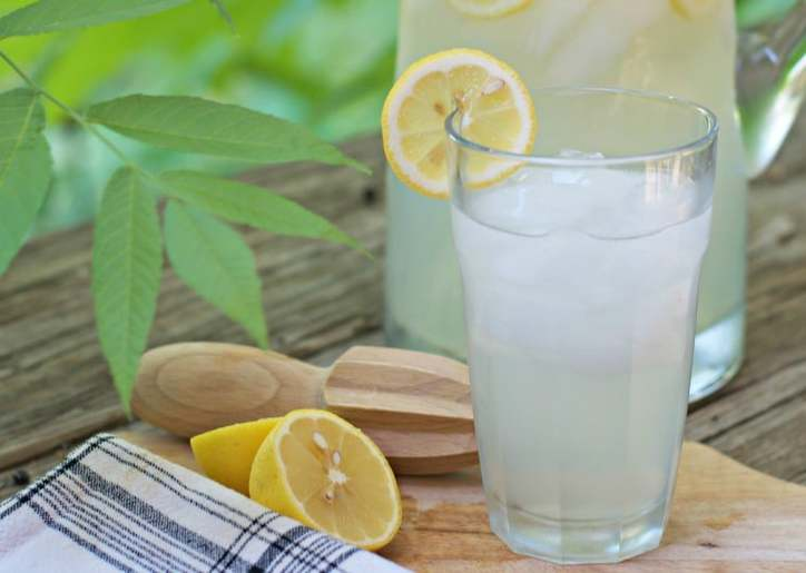 A close up photo of the lemonade glass with lemon on the rim and pitcher in the background