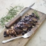 Blueberry Balsamic Chicken on a cutting board cut into slices wwith a sprig of Rosemary