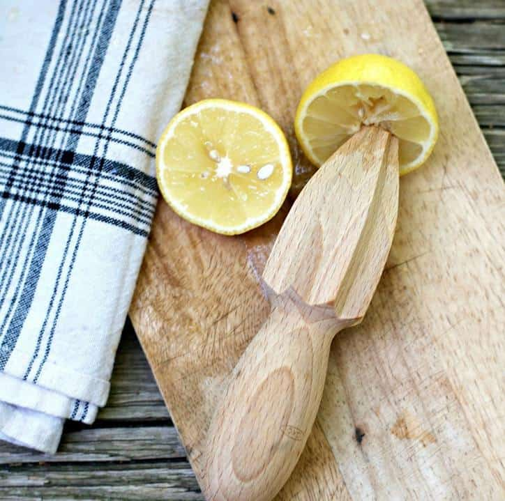 A photo of a lemon reamer that is wooden and a lemon cut in half