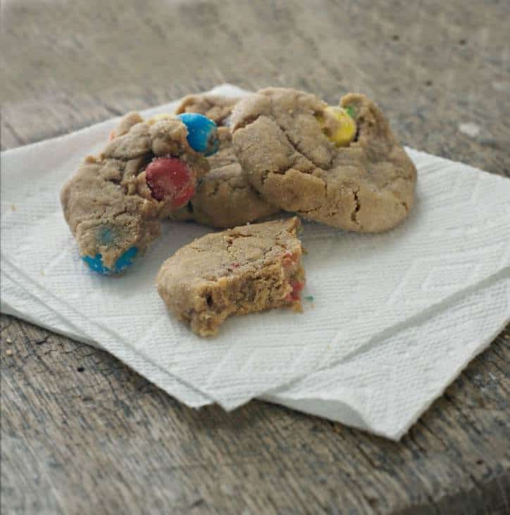 a photo of CARAMEL M&M'S KICKING BROWN SUGAR COOKIES with a bite taken out of one of them, sitting on a napkin