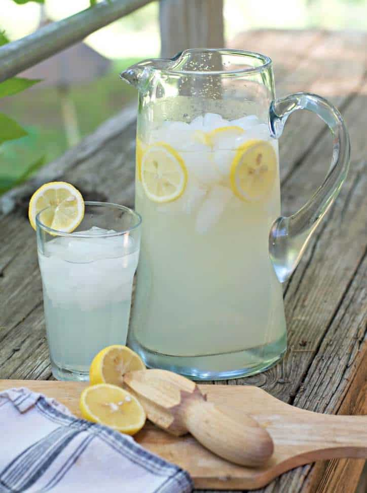 a photo ofFRESH HOMEMADE LEMONADE CONCENTRATE from farther off showing the pitcher and the glass and the reamer and the lemon
