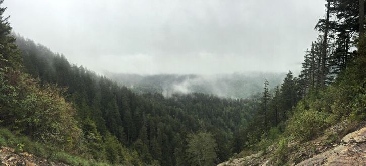 A photo of the mountain tops with fog and clouds laying on the mountain tops