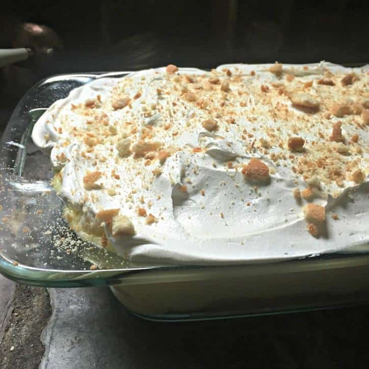 A photo of the finished cake from the side with cool whip topping and crushed vanilla wafers on top