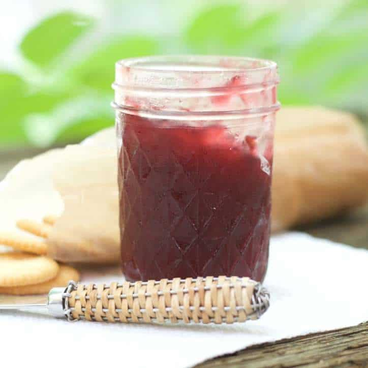 A photo of a cold jar of CARDAMOM PLUM JAM with a pack of crackers
