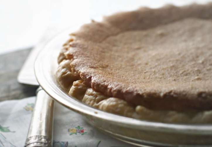 a photo of Old Fashioned Chess Pie from the side with delicate morning light shining across the pie