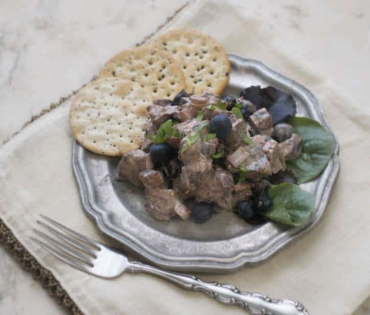 Blueberry Balsamic Chicken Salad on a pewter plate with crackers and fork to the side of the plate