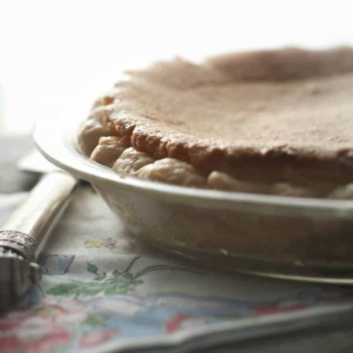 a whole pie from the side with morning light in the background flowered napkin and pie server