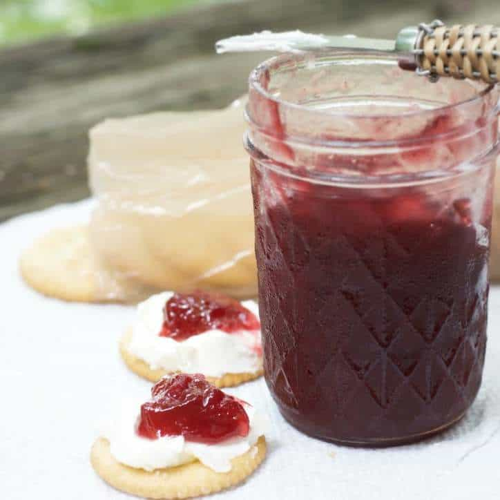a photo from the side of an open jar of CARDAMOM PLUM JAM with two crackers that have cream cheese and jam on them