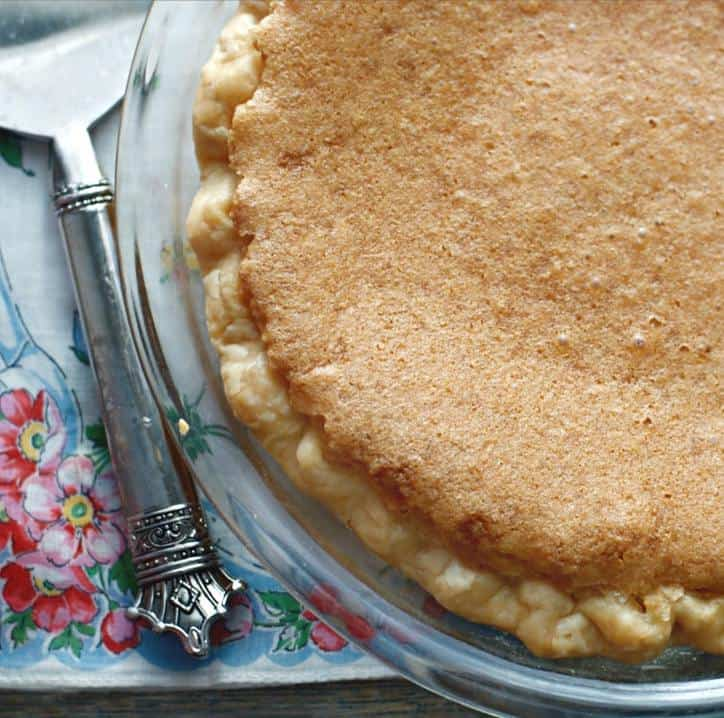 The upper crust of a chess pie in a glass pie plate with a silver serving handle and flowered napkin