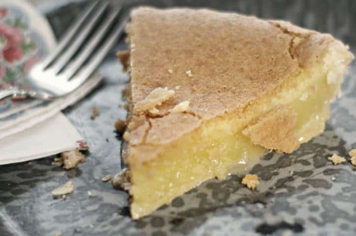 An upclose photo of Old Fashioned Chess Pie showing the gooey center starting to seep out onto the plate