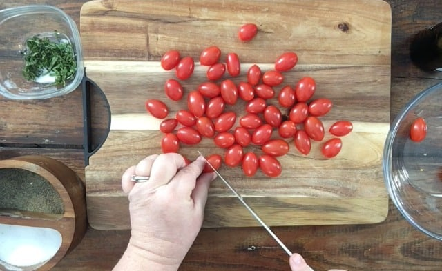 hand cutting a cherry tomato in half on cutting board. Cherry tomatoes in background