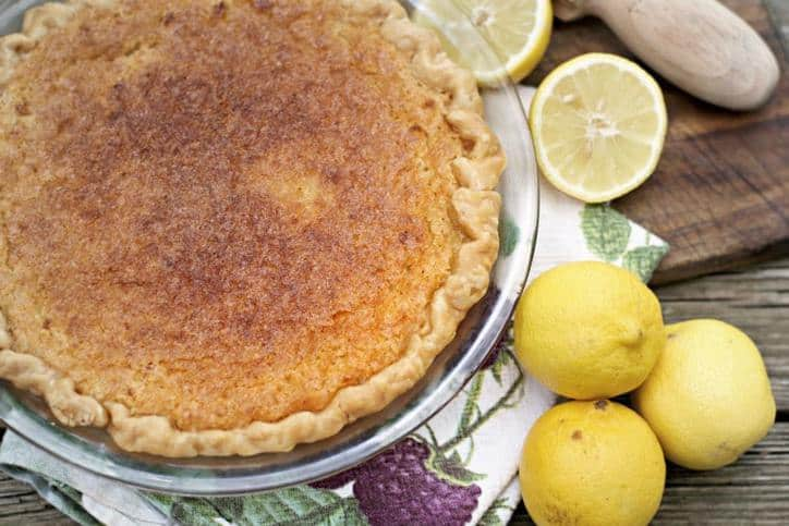 This is an overhead shot of a whole Old Fashioned Lemon Chess Pie with two lemons in the photo