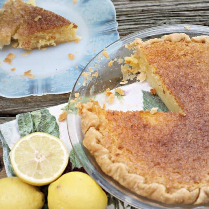 This is a photo of Old Fashioned Lemon Chess Pie with a slice out, you can see the slice in the photo as well as some lemons