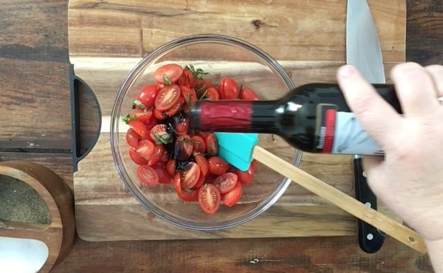 A bottle of balsamic vinegar being poured into the salad, blue spatula mixing in clear bowl on cutting board