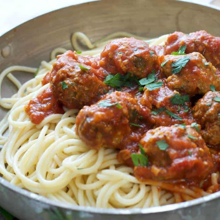 A very close up photo of the Blow Your Mind Meatballs in their serving dish over spaghetti noodles