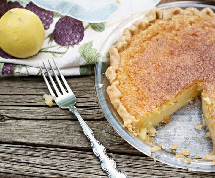 This is a photo of a Old Fashioned Lemon Chess Pie with a slice cut out a fork a lemon and a kitchen towel