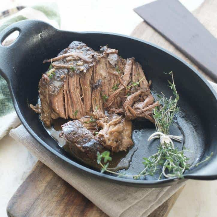 An overhead and to the side view of the crock pot roast recipe in an oval cast iron pan with thyme bundle and cutting board in the back ground
