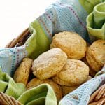 A photo of Southern Sweet Potato Biscuits in a basket with a blue and green kitchen towel
