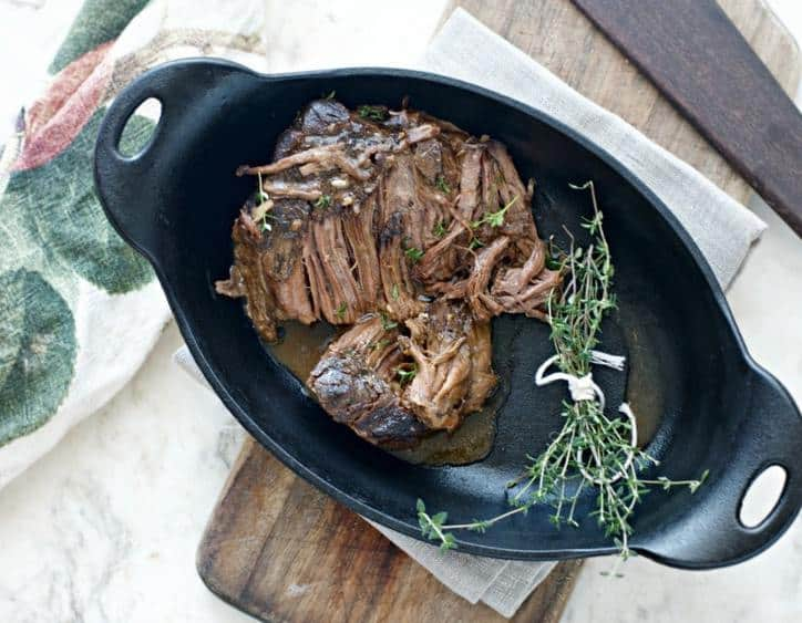 A directly overhead shot of rounded pan sitting on a cutting board with print towel in back ground. Chuck roast in the pan.