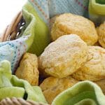 A close up shot of Southern Sweet Potato Biscuits in a basket with a blue and green kitchen towel under them