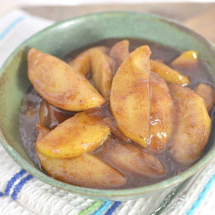 A green ceramic bowl full of cinnamon covered fried apples