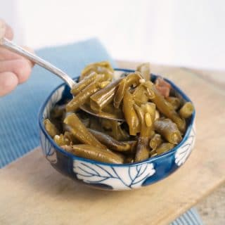 A photo of Slow Cooker Green Beans with Bacon with a spoon holding a bite