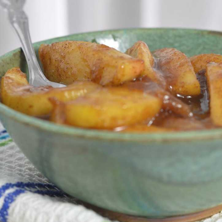 A photo of a green bowl of fried apples and spoon sitting on a white towel with blue stripes from the side THE SECRET TO PERFECT SOUTHERN FRIED APPLES