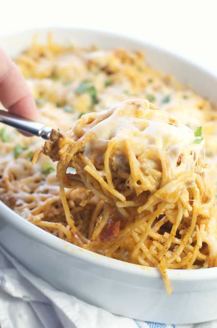 A spoonful of Amazing Baked Taco Spaghetti being scooped from the dish with cheese pulls