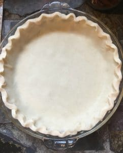 A photo of the pie crust with the edges fluted and ready to receive the pie ingredients for Kentucky Bourbon Pie
