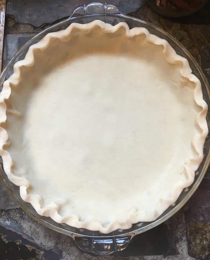 A photo of the pie crust with the edges fluted and ready to receive the pie ingredients.